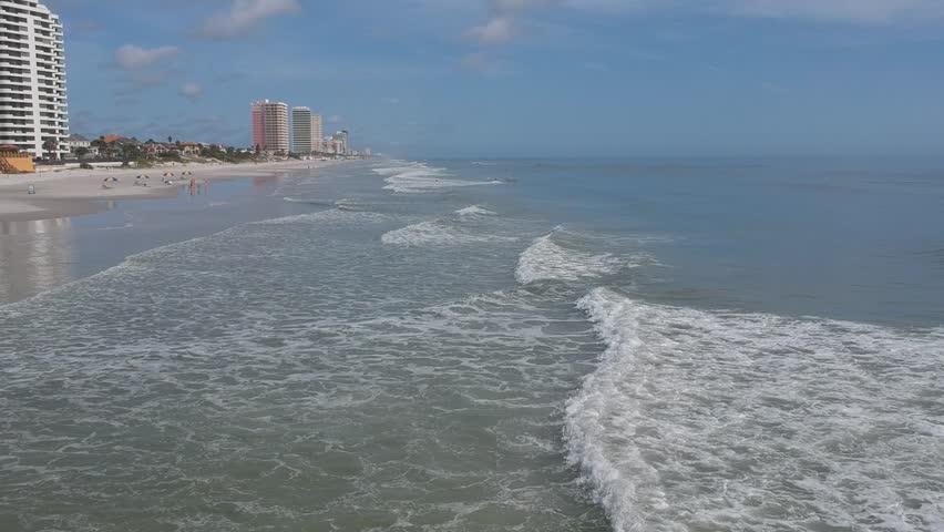 Aerial bird eye view of ocean waves crushing against the coast line of Daytona Beach, Florida. Royalty-Free Stock Footage #32068618