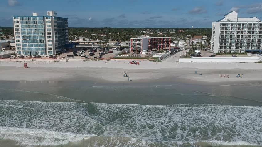 Aerial bird eye view of ocean waves crushing against the coast line of Daytona Beach, Florida. Royalty-Free Stock Footage #32068621