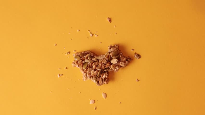 Granola bar bites stop motion on solid orange background with granola crumbs stopmotion