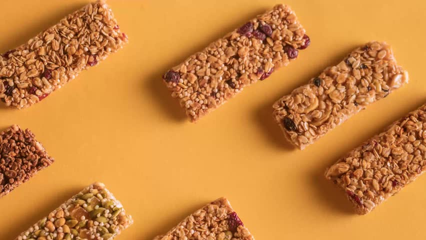 Different flavor granola stopmotion, bars moving along a solid orange background stop-motion from top-view