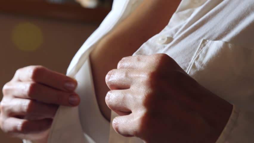Close-up, details. a woman buttoning the top button on a white shirt. 4k, slow motion