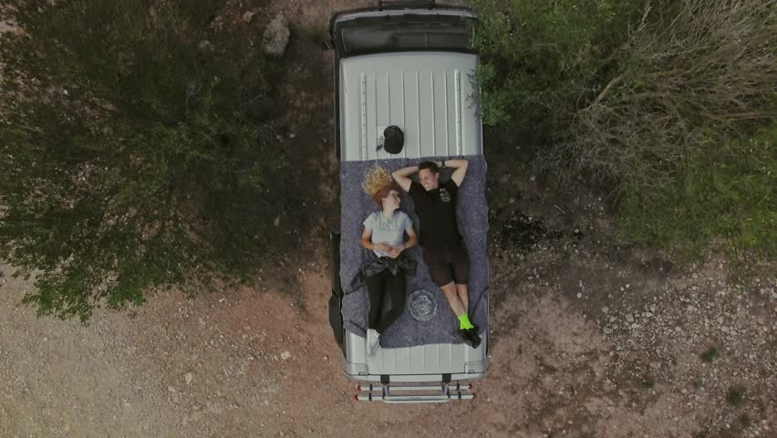 Top view with zoom out on romantic couple on date, laying on roof of car or van, watch stars or sky in natural national park, secluded camping site in wilderness, concept relationship goals or
