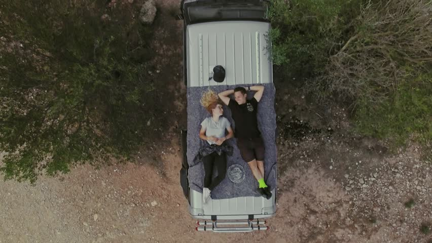 Top view on romantic couple on date, laying on roof of car or van, watch stars or sky in natural national park, secluded camping site in wilderness, concept relationship goals or millennials #32080345
