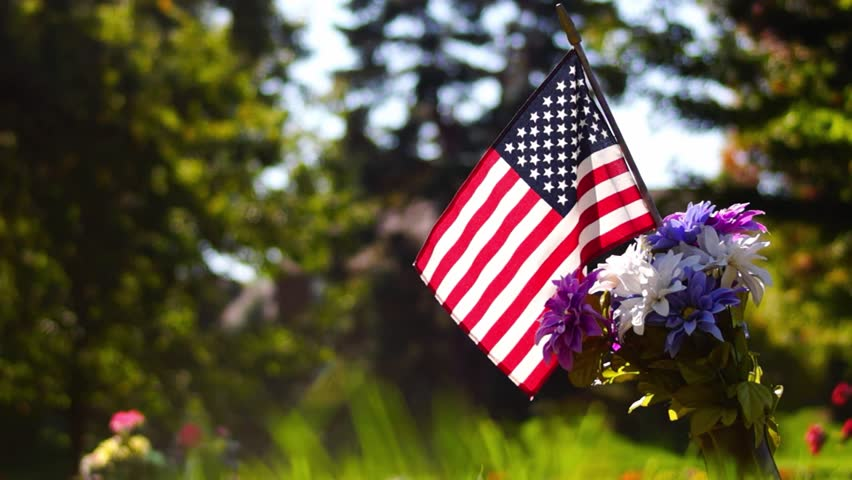 A soldier's grave is decorated with flowers and a little American flag in honor of service.