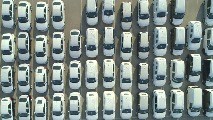 AERIAL TOP DOWN: Flying over big industrial zone with big parking lot of brand new cars. Many white cars waiting for sale and transportation at big sea port parking space. Heavy automobile industry.