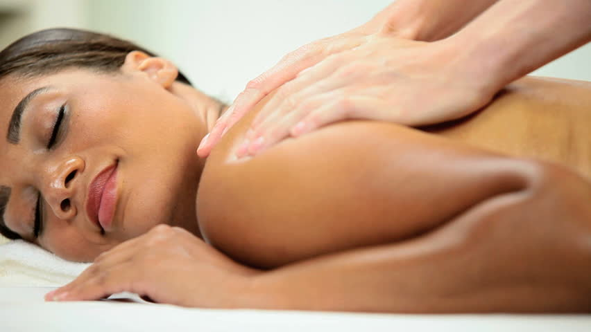 Health spa client receiving therapeutic body massage from a professional masseuse