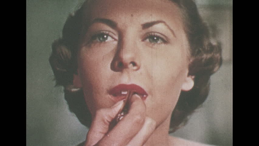 1950s: UNITED STATES: lady applies make up to lips. Lady inspects lipstick. Lady sits in front of mirror. Lady puts on top
