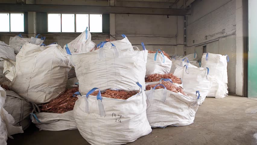 Huge white bags with copper scrap from wires are lying in a warehouse of scrap metal processing plant