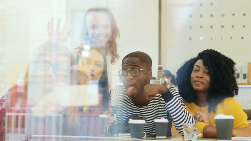 View through window of a mixed group of people sitting in the coffee shop and taking a selfie over coffee, making funny face and enjoying time together.   Shutterstock HD Video #32123641