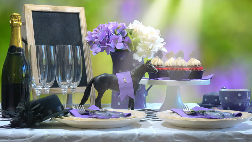 Horse Day Luncheon fine dining table setting with small black fascinator hat, decorations and champagne, wide static with lens flare.