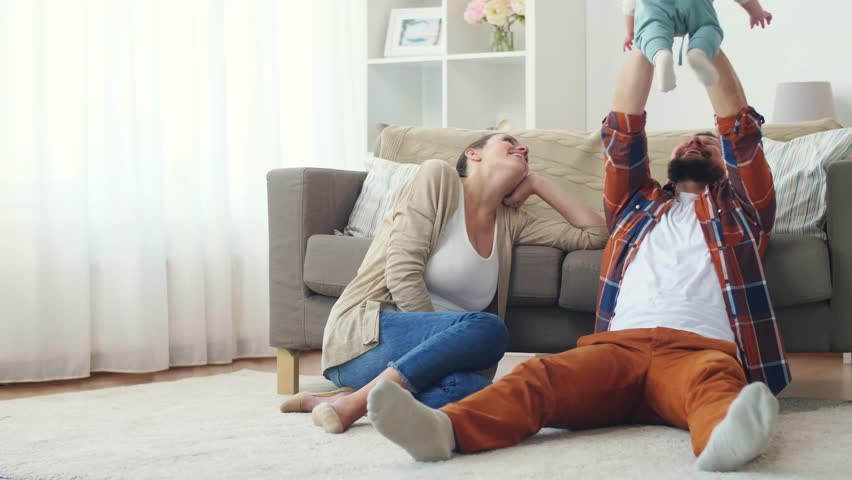 Family, parenthood and people concept - happy mother and father playing with baby at home | Shutterstock HD Video #32137447