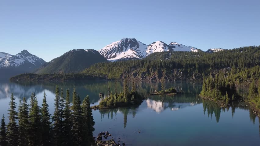 Aerial landscape view of the beautiful rocky islands in glacier lake with mountains in the background. Picture taken in Garibaldi near Squamish, North of Vancouver, British Columbia, Canada.