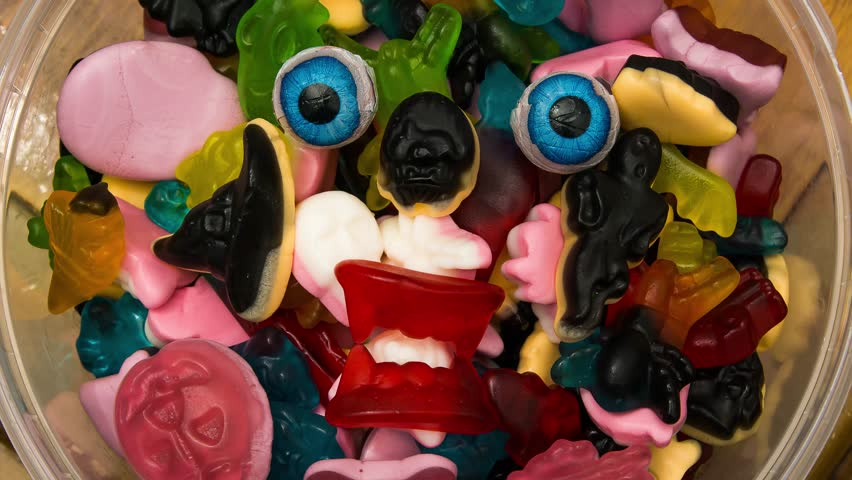 A halloween candy monster in a bowl of haloween candy eyeballs glaring at one on top of sweets someone taking an piece to eat.