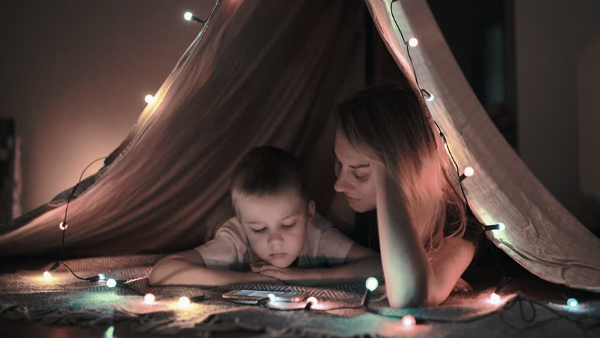 Mother and son play and watching smartphone in children's room in tent with Christmas decorations #32155087