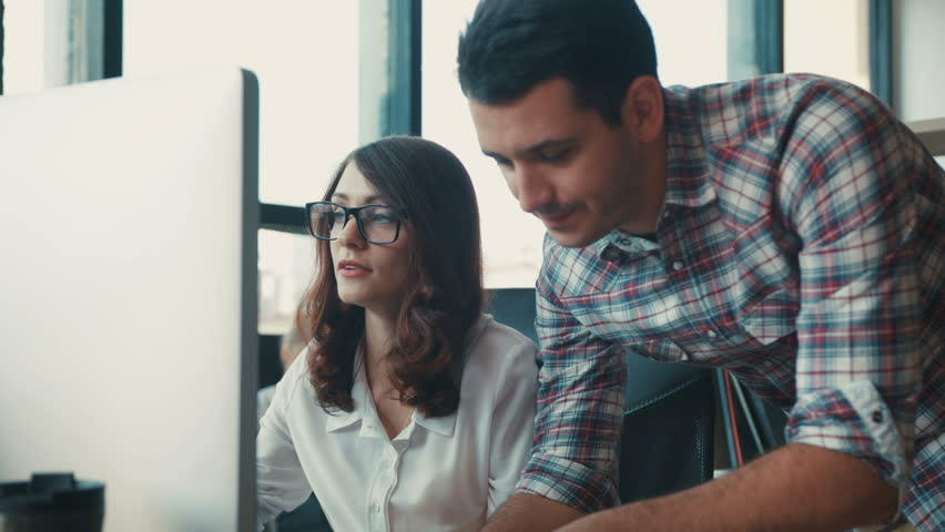 Close up man and woman are working on computer in a loft while discussing a project  | Shutterstock HD Video #32163247