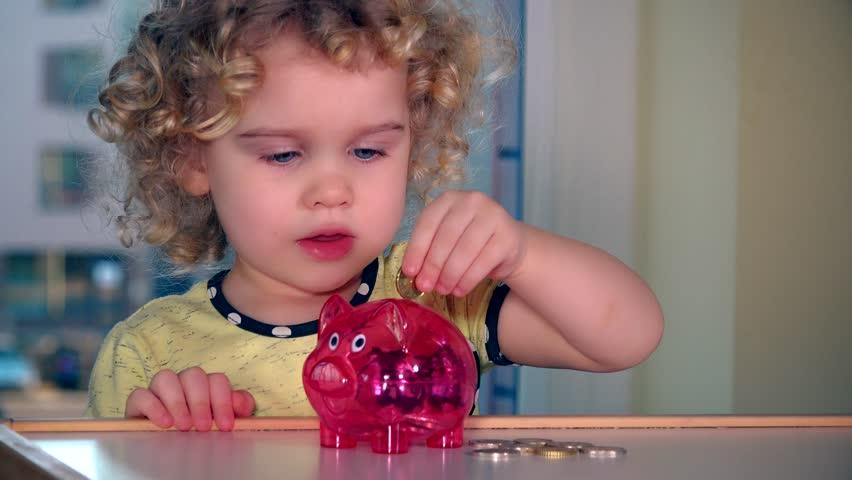 Cute little girl insert euro coins into piggybank. Static shot. 4K UHD
