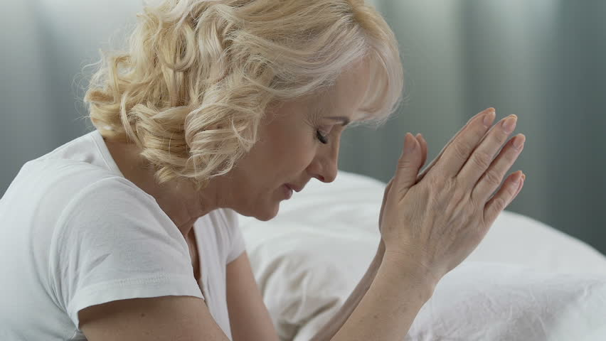Woman of senior age praying at her bed, eyes closed, smiling, gratitude to God