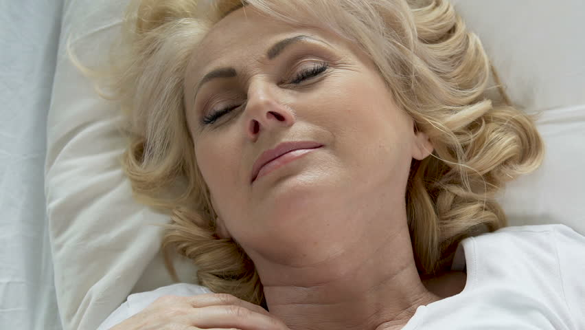 Aged lady lying in bed, rubbing face after good sleep, night cream, cosmetics