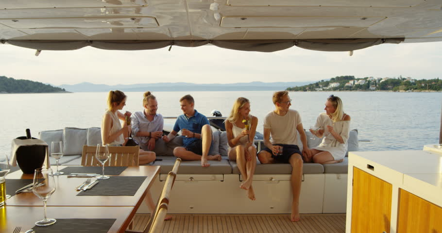 Group of Successful Young People Have Great Time in the Stern of a Yacht, They Drink Cocktails, Talk and Have Fun. In the Background Sea and Islands. Shot on RED Epic 4K UHD Camera.