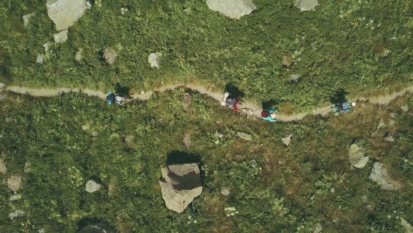 Aerial shooting from flying drone hiking group walking on mountain trail. Tourist group traveling in mountain valley. Hiking tour in mountain. Mountain trip