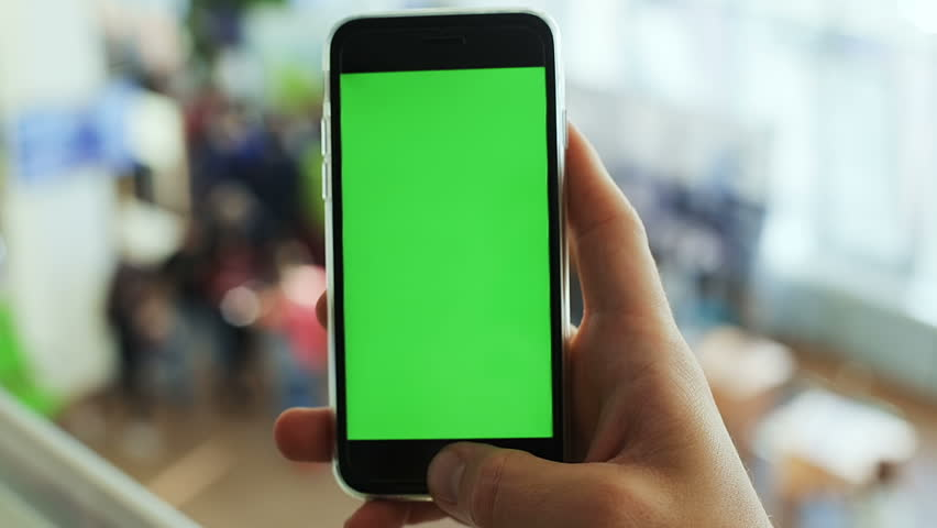 Man hand holding cellphone university hall smartphone public space green screen mockup chromakey blur background people checking news notification map gps chatting apps internet connect online reading | Shutterstock HD Video #32205610
