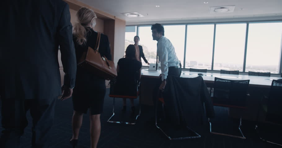 Businesspeople entering a conference room for business meeting. Executives arriving for meeting and shaking hands with colleagues.