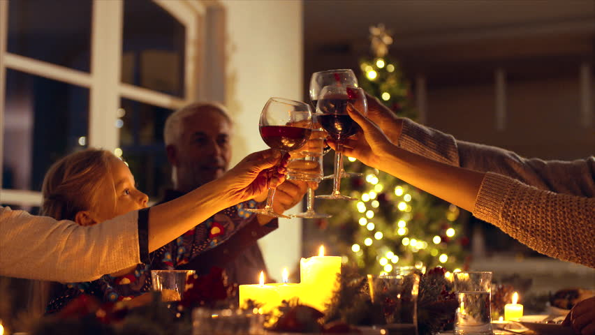 Family toasting wine at christmas dinner. Family enjoying christmas dinner together at home, with focus on hands and wine glasses.