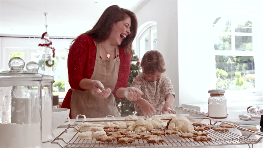 Smiling mother and daughter playing with cookie flour at kitchen counter while making Christmas cookies. Baked cookies and muffins on tray for Christmas. #32229793