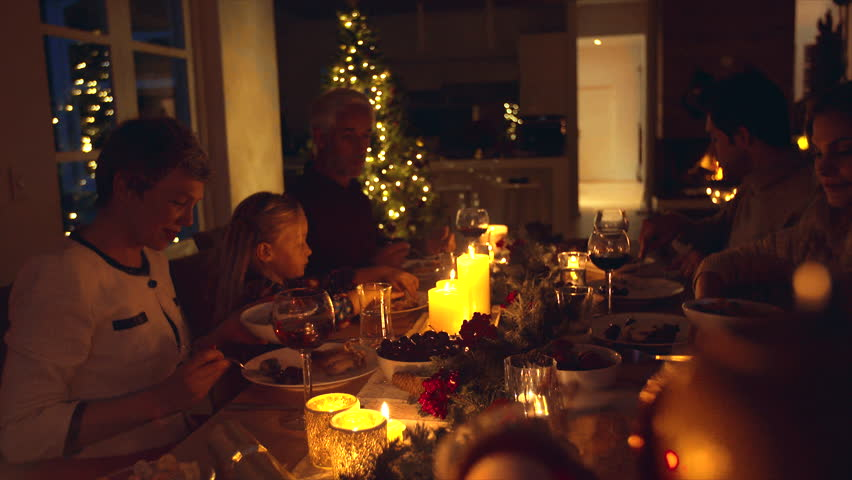 Christmas eve dinner, family sitting at dining table enjoying dinner together. Family celebrating christmas together at home. | Shutterstock HD Video #32229808