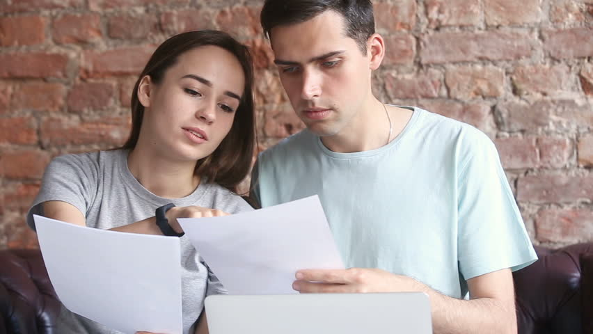 Young man and woman having problems with documents, confused couple looking through papers sitting at home with laptop, checking unpaid bills, worried about overdue debt, searching legal help online