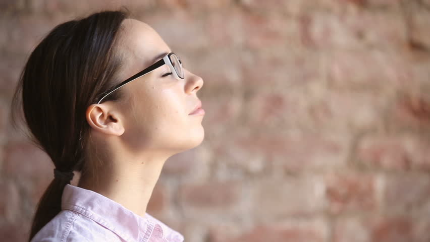 Young woman wearing glasses inhaling and exhaling fresh air, taking deep breath, enjoying practicing breathing pranayama exercises indoors, calming down, reducing stress, close up face side view