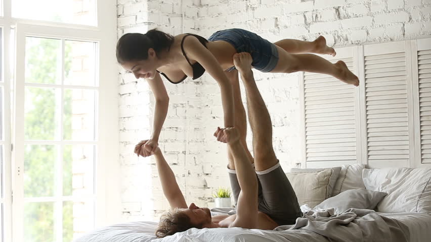 Fit sporty couple practicing acro yoga with partner together on bed, performing front plank bird pose, young man holding flying womans arms balancing on his feet, doing acrobatic exercise at home