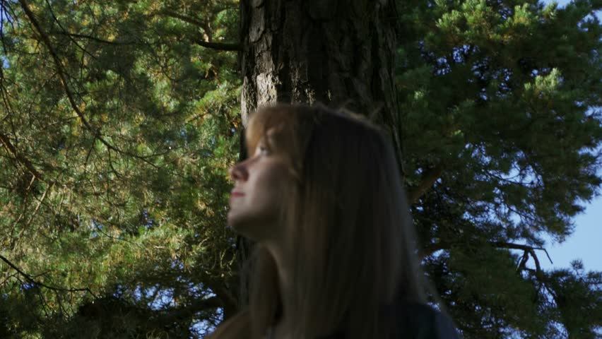 A beautiful girl wanders through the forest. The girl was lost. In the background, the sky.