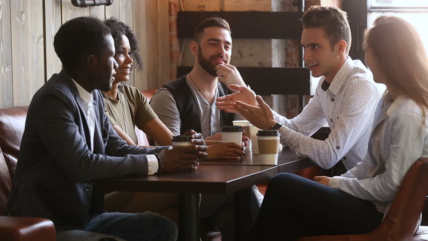 African and caucasian buddies making bet shaking hands at group meeting in coffeehouse, positive diverse young friends telling funny joke, laughing having fun while relaxing in cozy cafe with coffee