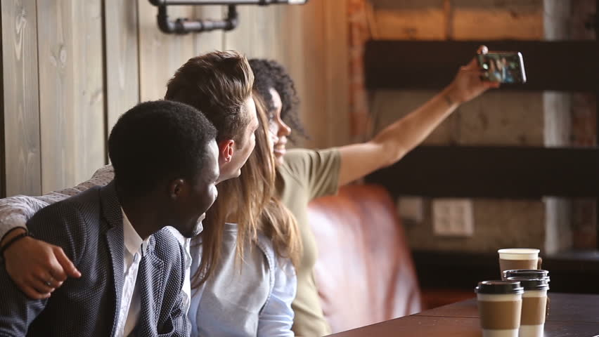 African woman taking group selfie at meeting with diverse friends in coffeeshop, multiracial young people making photo together on cafe couch, multi-ethnic happy students photographing on smartphone