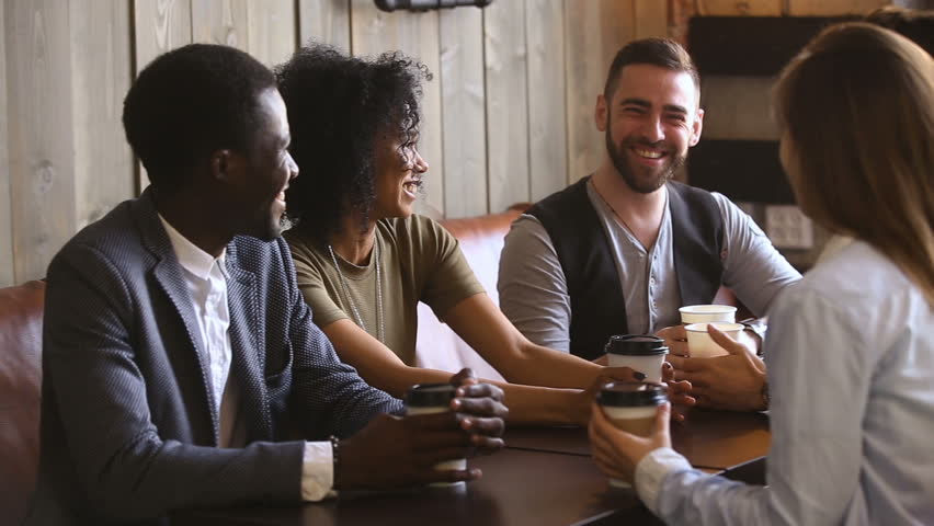 Diverse young guys spending time together in cafe, multinational close best friends talking and laughing at meeting in cafeteria, positive mates enjoying hanging out together relaxing in coffee house