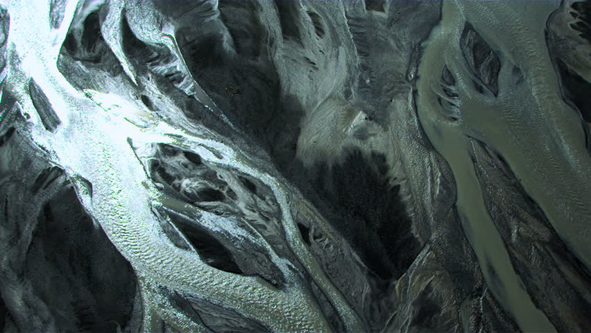 Aerial view of glacial meltwaters and volcanic ash in river deltas carving through flood plains, arctic region, Northern Hemisphere