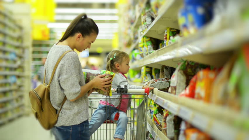 Young Attractive Mom and Little Child Buying Food in a Supermarket. Beautiful Woman with Cute Girl Standing Near Shelf With Goods Looks Carefully on Every Products Hold in Her Hand. | Shutterstock HD Video #32244916
