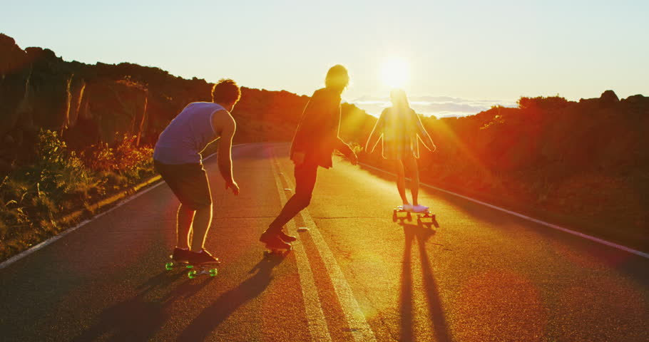 Skateboarders riding down hill into the sunset