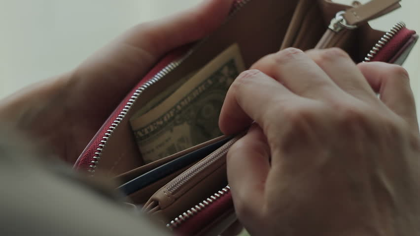 A woman opens her wallet and looks for money in it, but finds only one dollar in it