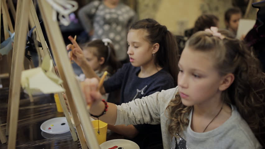 beautiful teenage girl sitting at the easel paints a picture in an art school. Professional art school for children Royalty-Free Stock Footage #32279023