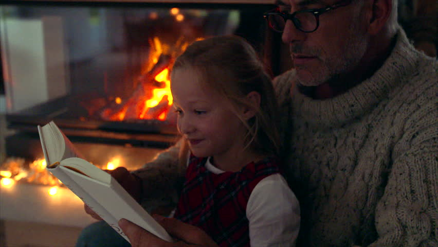 Senior man reading a book to little girl near fireplace. Senior man with grandaughter reading a story book.