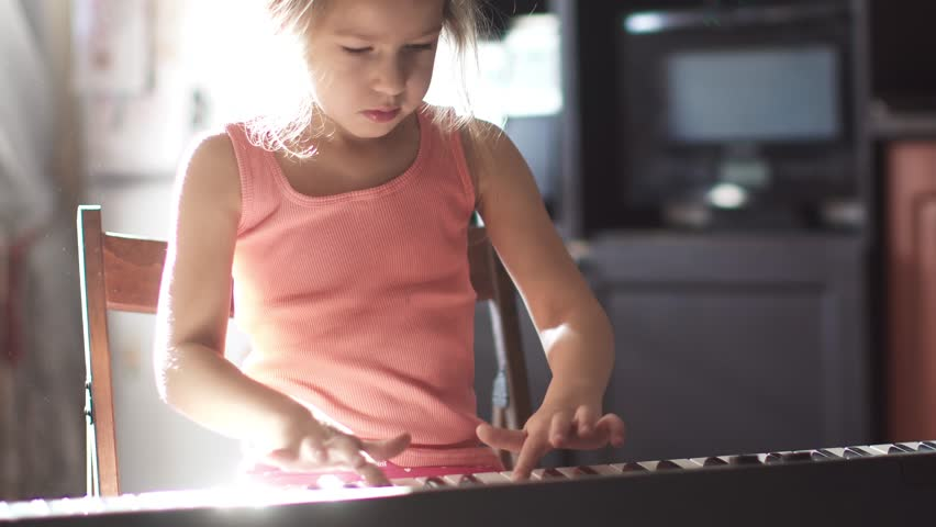 child is playing the piano at home. the little girl is learning to play the electronic piano. girl in the sunlight