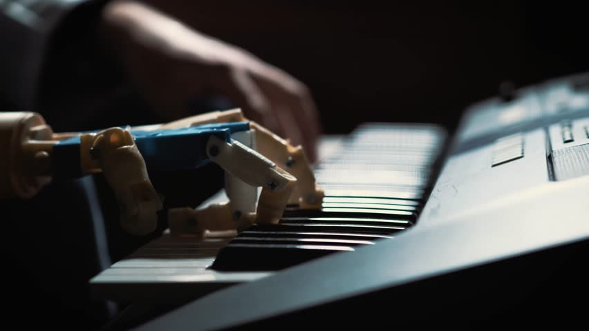 Man musician pianist with a prosthetic hand playing the piano. He plays with two hands, a robot hand and a human hand. Robot creates music and art.