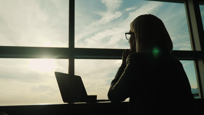 A woman in a business suit looks out the window of her office. Concept - look ahead in business #32298199