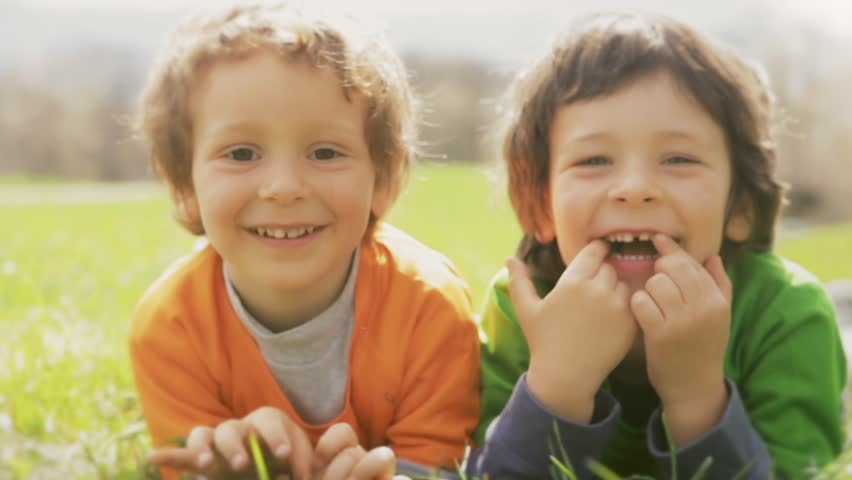 Happy children smiling close up portrait. Two brother kids laughing and playing while lay down on grass meadow in outdoor sunny day. Family son boys relaxing in nature.video footage | Shutterstock HD Video #32300623