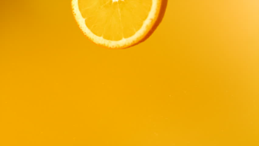 Sliced orange falling into orange juice shooting with high speed camera, phantom flex.