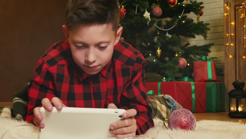 Boy playing with his digital tablet on Christmas Eve | Shutterstock HD Video #32301676