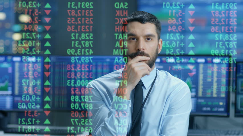 Stock Market Top Trader Looks at Projected Ticker Numbers and Graphs Running, Analysing Data to Make Best Sell. Behind Him Room Full of Screens and Statistics. Shot on RED EPIC-W 8K Cinema Camera.