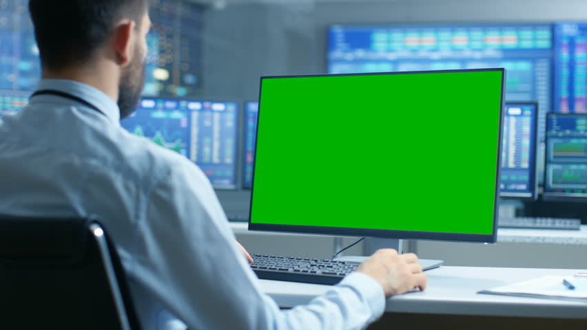 Over the Shoulder View of Stock Market Trader Working on a Computer with Isolated Mock-up Green Screen. In the Background Monitors Show Stock Ticker Numbers and Graphs. Shot on RED EPIC-W 8K Camera. | Shutterstock HD Video #32305306
